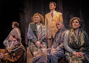 JIn America oseph Hollander (Sean Fortunato) receives letters from his family in Poland who would not leave when they could because they thought they were safe. L to R Doola (Patricia Lavery), Lusia (Mikey Gray), Genka (Brenann Stacker) Gerta (Glynis Bell), Salo (Ron E. Rains) and Maria (Amy J. Carle). Photo by Liz Lauren