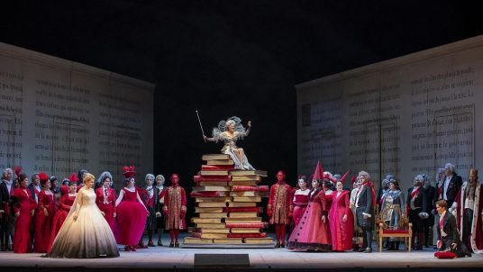Cinderella (Siobhan Stagg) far left, Fairy godmother (Maie-Eve Munger) atop the books center and Prince charming (Alice Coote) far right kneeling with cast of Cenrillon at the Lyric Opera.