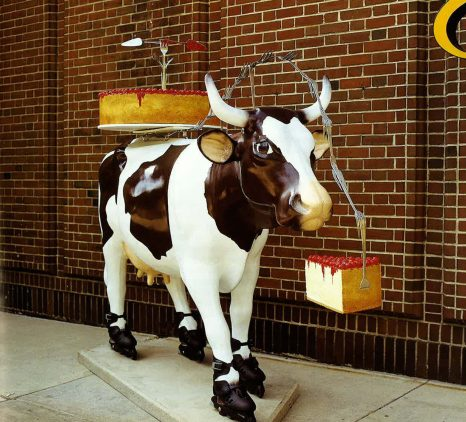 Mooving Eli. Eli, the cow, sports roller blades to keep on moovin' toward a big slice of cherry topped cheesecake! Eli is also carrying a large cherry cheesecake with a fork and cake server sculpture in case he runs into any other cows and wants to have a dessert party. Eli's spots are in the shape of the state of Illinois. (Photo courtesy of Magnificent Mile Asociation and Eli's Cheesecake.)